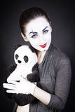 A woman mime with a toy panda Stock Images