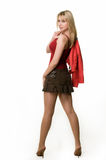 Woman in mini skirt. Full body of an attractive young blond woman wearing short cute brown skirt and red tank top with jacket off standing looking over shoulder Royalty Free Stock Image