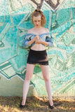 Woman in Mini Skirt Against Graffiti Covered Wall Stock Photo