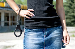 Woman in mini skirt holding handcuffs. Royalty Free Stock Photography