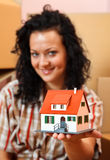 Woman with miniature house. Attractive young woman offering a miniature house, boxes in the background Stock Photo