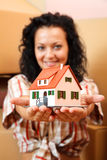 Woman with miniature house. Attractive young woman offering a miniature house, boxes in the background Royalty Free Stock Image