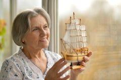 Woman with miniature ship Stock Photos