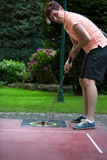 Woman at a minigolf court hits a black ball with an iron racket Stock Images