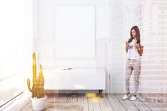 White living room, closet and poster, woman. Woman in minimalistic living room with white walls, wooden floor, a white and wooden closet with a book on it and royalty free stock image