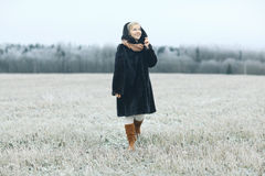 Woman in  mink coat walks in winter field Royalty Free Stock Photos