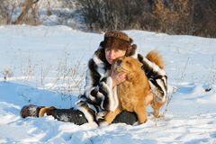The woman in a mink fur coat plays with a dog Stock Photo