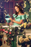 woman in mint dress watering flowers on a porch of her house Royalty Free Stock Photography