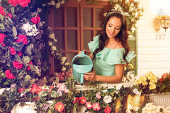 Woman in mint dress watering flowers on a porch of her house Stock Photo