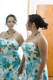 The woman in the mirror. Latino woman looking at herself in a doorway mirror Royalty Free Stock Images