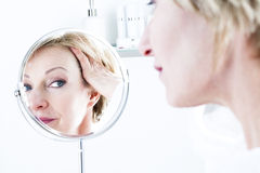 Woman In The Mirror. Mature Woman In The Mirror Stock Photography