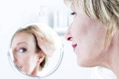 Woman In The Mirror. Woman looking  in the mirror Stock Photos