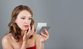 Woman with mirror Stock Images