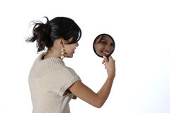Woman with mirror. Attractive young woman in a tight dress looking at herself in a mirror Stock Images