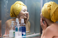 Woman mirror bathroom. Cheerful woman with towel on head having a look at her face at mirror in bathroom stock photos