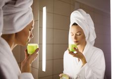 Woman and mirror in bathroom. Holding cream. In hand stock photo