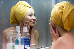 Woman mirror bathroom. Portrait of young smiling woman wearing towel after shower looking at herself in mirror royalty free stock photo