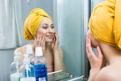 Woman mirror bathroom. Portrait of young smiling woman wearing towel after shower looking at herself in mirror stock photo