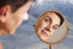 Woman in the mirror on blue Royalty Free Stock Image