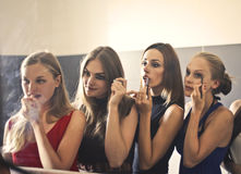 Woman in the mirror. Woman are doing their make up Royalty Free Stock Photography
