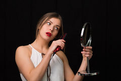 Woman with a mirror and flat hair iron Stock Photos