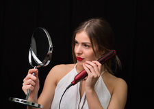 Woman with a mirror and flat hair iron Royalty Free Stock Photo