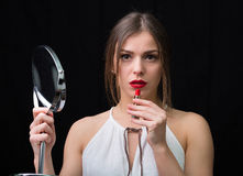 Woman with a mirror and a red lipstick Royalty Free Stock Photography