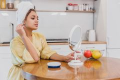 Woman in the mirror of the bathroom make a makeup. The natural beauty of a woman. Woman in the mirror of the room make a makeup. The natural beauty of a woman royalty free stock photo