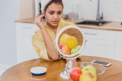 Woman in the mirror of the bathroom make a makeup. The natural beauty of a woman. stock photos