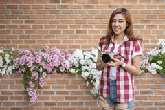 Woman with mirrorless camera. On brick wall background royalty free stock photo