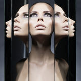 Woman and mirrors. Fashion studio portrait of woman and mirrors on black background Royalty Free Stock Image
