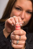 Woman misbehaving with rubber band. Close-up of young woman aiming rubber band - focus on thumb Stock Photo