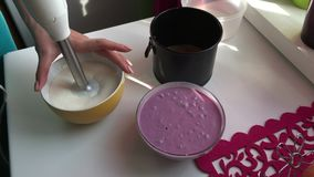 The woman mixes blender with the dissolved gelatin, jam and cottage cheese. stock video footage