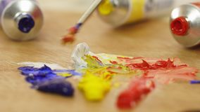 The woman mixes paints on a palette. White. Red. Blue. Yellow. Oil paints. Palette of paints. The artist prepares paints stock video footage
