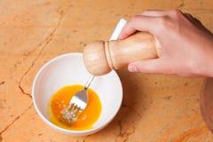 Woman mixing eggs in white bowl Royalty Free Stock Photos