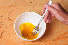 Woman mixing eggs in white bowl Stock Image