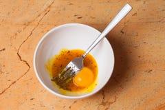 Woman mixing eggs in white bowl Stock Photo
