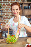 Woman mixing fresh vegetable salad. Smiling woman in apron mixing fresh vegetable salad in kitchen Stock Photos