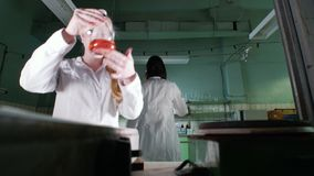 A woman is mixing a orange liquid. A woman is mixing orange liquid in medical laboratory stock footage
