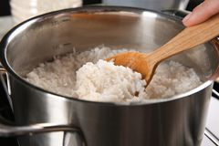 Woman mixing rice in pan. With spoon Stock Photography