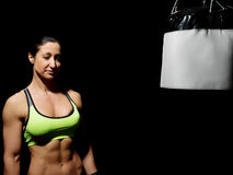 Woman in mma gloves fighting with boxing bag Stock Photo