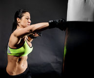 Woman in mma gloves fighting with boxing bag Royalty Free Stock Images