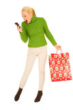 Woman with mobile and bags with Christmas gifts. On white background Royalty Free Stock Image
