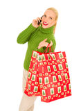 Woman with mobile and bags with Christmas gifts. On white background Stock Photo