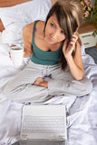 Woman with mobile on bed Royalty Free Stock Images