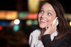 Woman with mobile cell phone over night city Stock Image