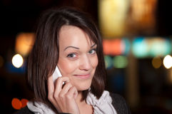 Woman with mobile cell phone over night city Royalty Free Stock Photo