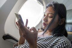 A woman with mobile on a flying plane stock photo