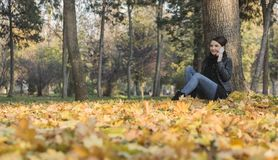 Woman with a Mobile in a Forest in the Autumn Royalty Free Stock Photo