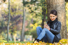 Woman with a Mobile in a Forest in the Autumn. Portrait of a young woman with a mobile sitting in a yellow autumn forest Stock Images
